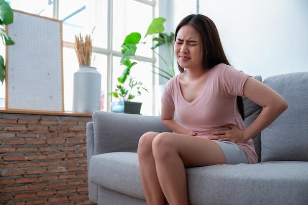 Jovem mulher asiática que sente a dor abdominal ao sentar-se no sofá do sofá na sala de visitas em casa.