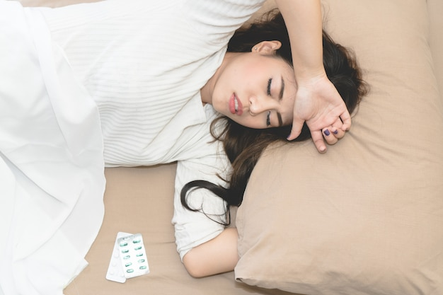 Jovem mulher asiática que sofrem de febre.