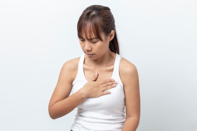 Jovem mulher asiática que tem a dor no peito severa que sofre do ataque cardíaco isolado no fundo branco.