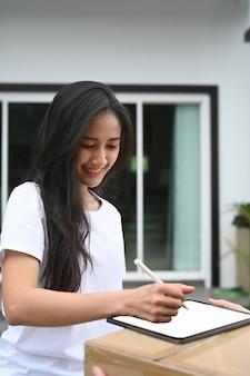 Jovem mulher asiática recebe caixa do entregador e assinatura no tablet digital.