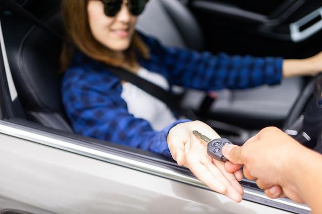 Jovem mulher asiática recebendo as chaves do seu carro novo.