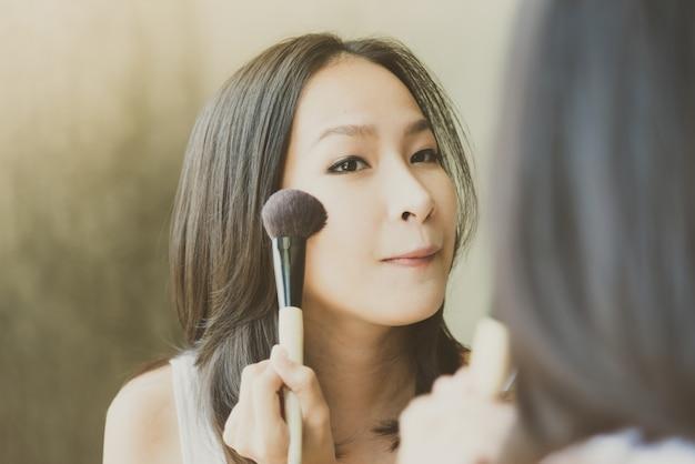 Jovem mulher asiática se maquiar
