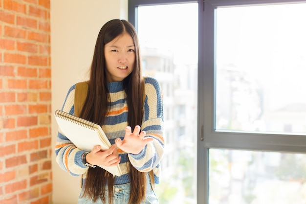 Jovem mulher asiática se sentindo enojada e com náuseas, se afastando de algo desagradável, fedorento ou fedorento, dizendo eca