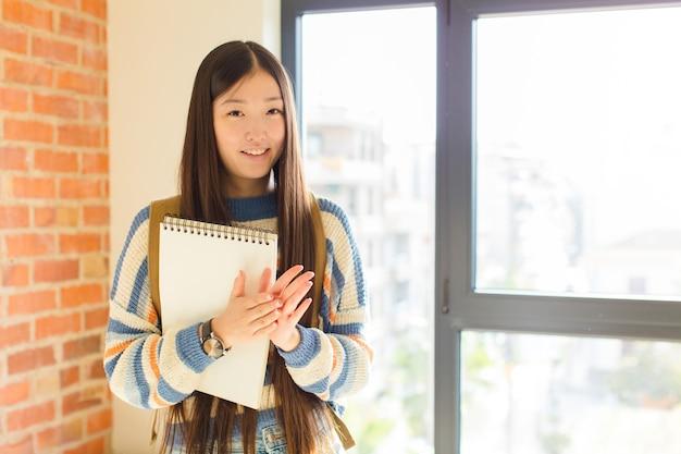 Jovem mulher asiática se sentindo feliz e bem-sucedida, sorrindo e batendo palmas, dizendo parabéns com aplausos