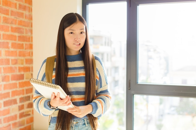 Jovem mulher asiática se sentindo sem noção, confusa e incerta sobre qual opção escolher, tentando resolver o problema