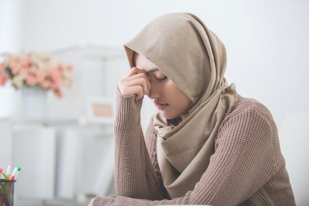 Jovem mulher asiática segura sua cabeça pensando em algo
