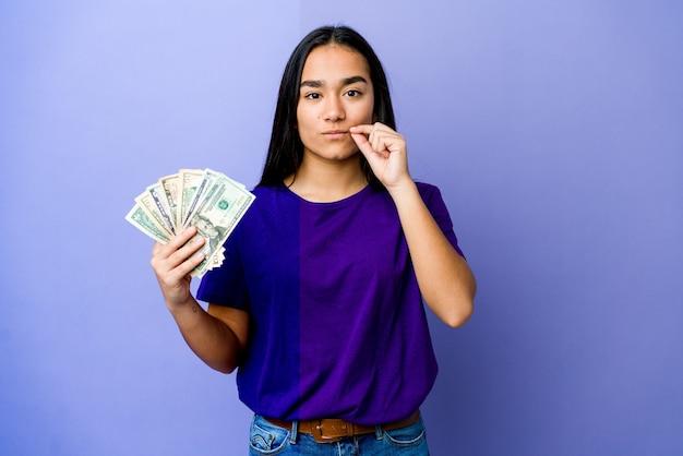 Jovem mulher asiática segurando dinheiro isolado em um fundo roxo com os dedos nos lábios, mantendo um segredo.