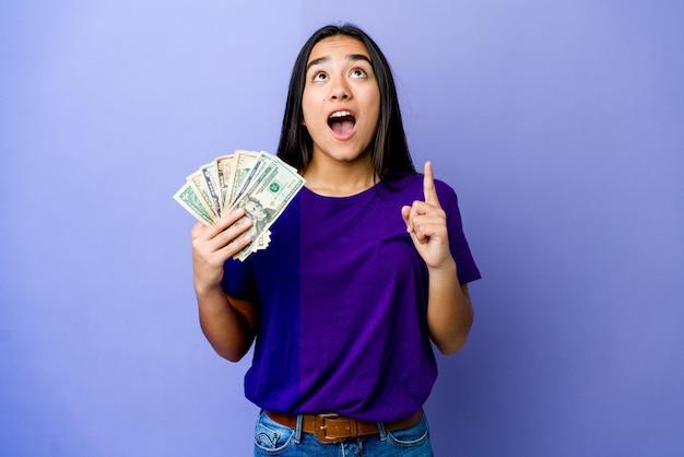 Jovem mulher asiática segurando dinheiro isolado na parede roxa, apontando para cima com a boca aberta.