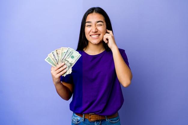 Jovem mulher asiática segurando dinheiro isolado na parede roxa, cobrindo as orelhas com as mãos.