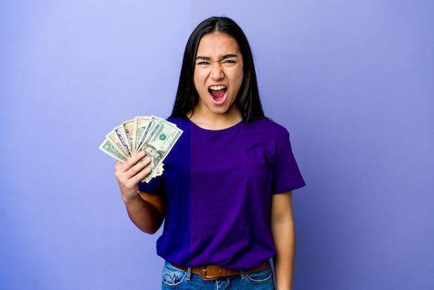 Jovem mulher asiática segurando dinheiro isolado na parede roxa, gritando muito zangada e agressiva.