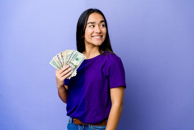 Jovem mulher asiática segurando dinheiro isolado na parede roxa parece de lado sorrindo, alegre e agradável.