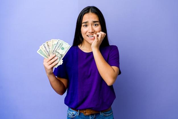 Jovem mulher asiática segurando dinheiro isolado na parede roxa, roendo as unhas, nervosa e muito ansiosa.