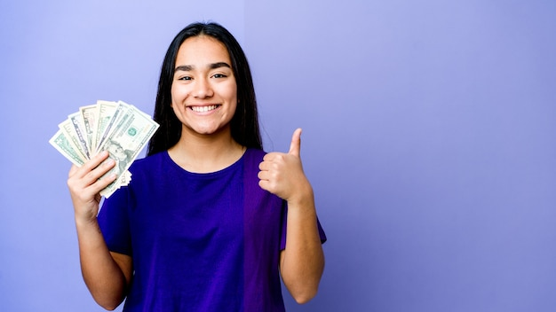 Jovem mulher asiática segurando dinheiro isolado na parede roxa, sorrindo e levantando o polegar