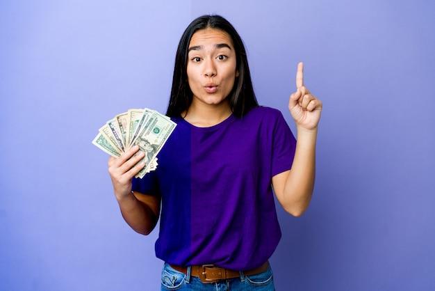Jovem mulher asiática segurando dinheiro isolado na parede roxa, tendo uma ótima ideia, o conceito de criatividade
