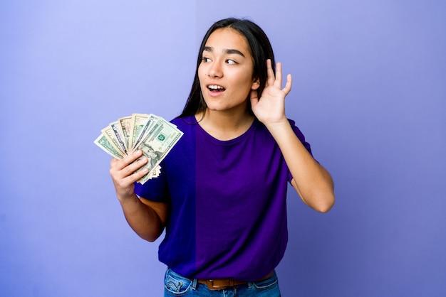 Jovem mulher asiática segurando dinheiro isolado na parede roxa, tentando ouvir uma fofoca