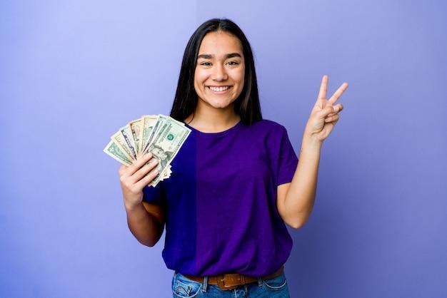 Jovem mulher asiática segurando dinheiro isolado no roxo, alegre e despreocupada, mostrando um símbolo de paz com os dedos.