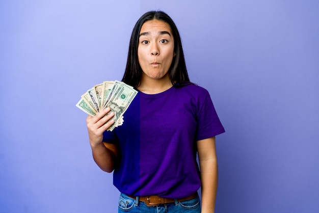 Jovem mulher asiática segurando dinheiro isolado no roxo encolhe os ombros e abre os olhos confusos.