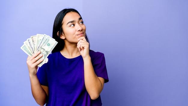 Jovem mulher asiática segurando dinheiro isolado no roxo, olhando de soslaio com expressão duvidosa e cética.