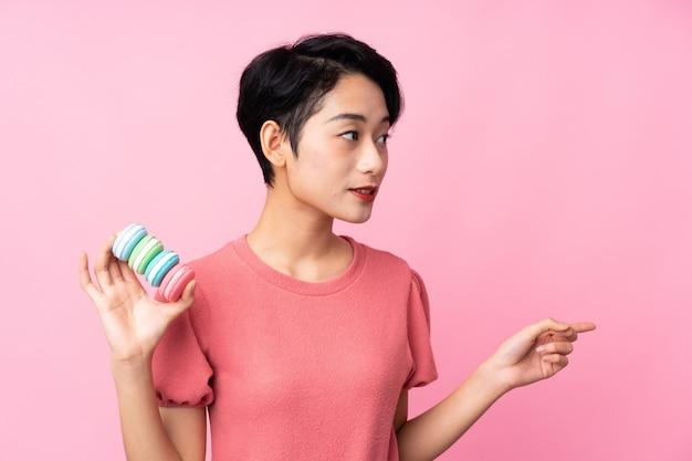 Jovem mulher asiática segurando macarons franceses coloridos e apontando o lado