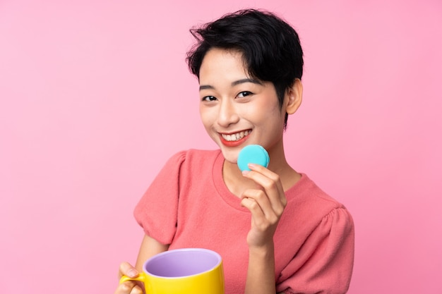 Jovem mulher asiática segurando macarons franceses coloridos e um copo de leite