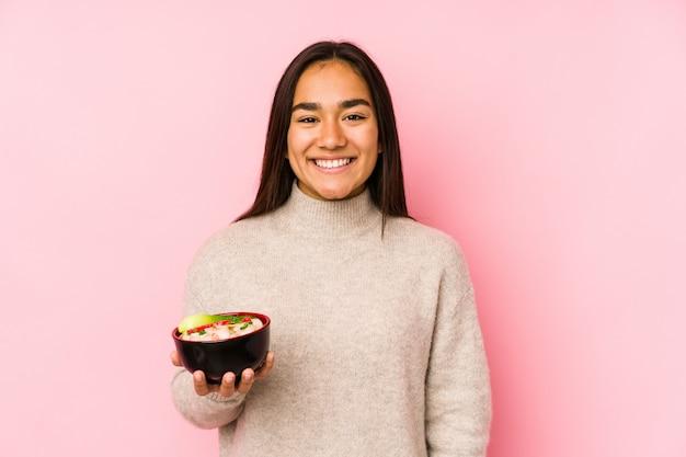 Jovem mulher asiática segurando macarrão feliz, sorridente e alegre.