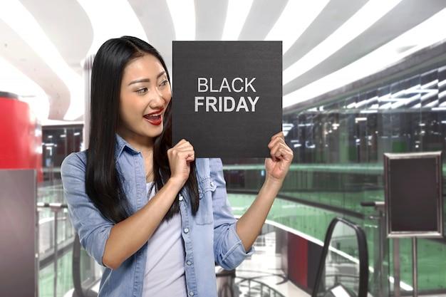 Jovem mulher asiática segurando placa de sinal com texto de sexta-feira negra