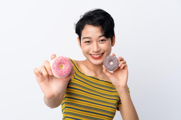 Jovem mulher asiática segurando rosquinhas com expressão feliz