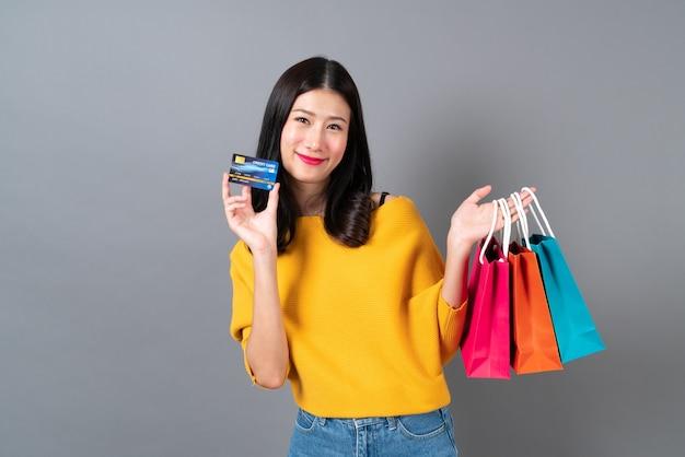 Jovem mulher asiática segurando sacolas de compras e cartão de crédito em camisa amarela cinza