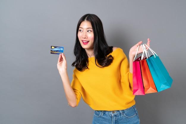Jovem mulher asiática segurando sacolas de compras e cartão de crédito em uma camisa amarela sobre fundo cinza