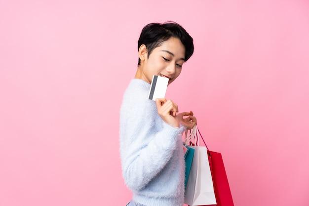 Jovem mulher asiática segurando sacolas de compras e cartão de crédito