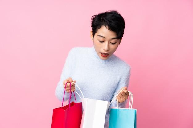 Jovem mulher asiática segurando sacolas de compras e olhando para dentro