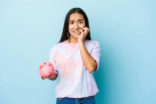 Jovem mulher asiática segurando um banco rosa sobre a parede isolada, roendo as unhas, nervosa e muito ansiosa.
