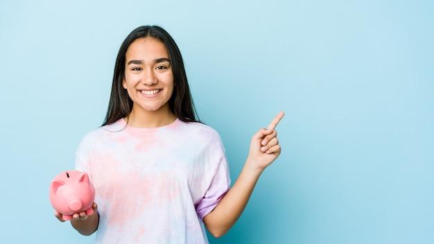 Jovem mulher asiática segurando um banco rosa sobre uma parede isolada, sorrindo e apontando para o lado, mostrando algo no espaço em branco