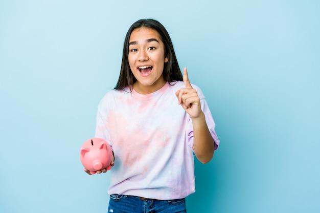 Jovem mulher asiática segurando um banco rosa sobre uma parede isolada, tendo uma ideia, um conceito de inspiração