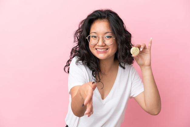 Jovem mulher asiática segurando um bitcoin isolado em um fundo rosa apertando as mãos para fechar um bom negócio