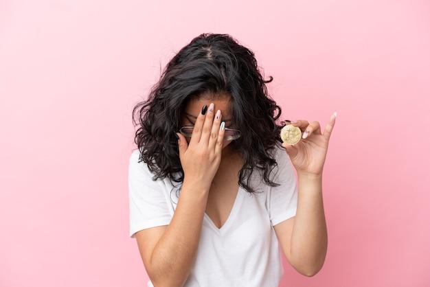 Jovem mulher asiática segurando um bitcoin isolado em um fundo rosa com expressão de cansaço e doentia