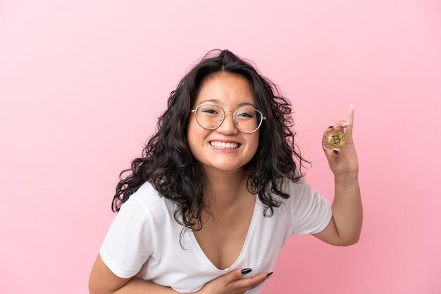Jovem mulher asiática segurando um bitcoin isolado em um fundo rosa e sorrindo muito