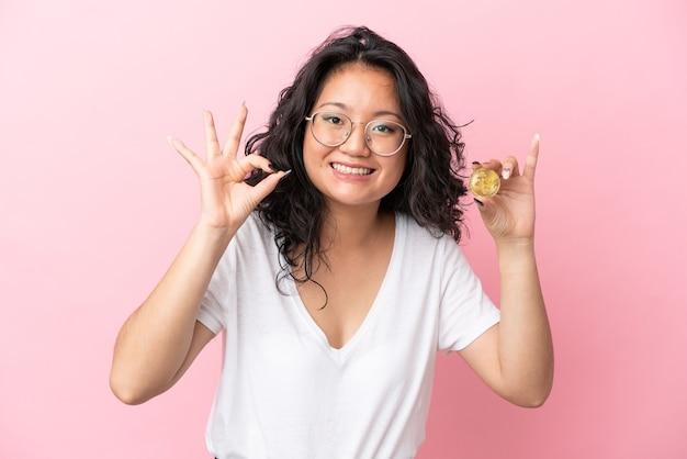 Jovem mulher asiática segurando um bitcoin isolado em um fundo rosa, mostrando um sinal de ok com os dedos