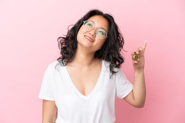 Jovem mulher asiática segurando um bitcoin isolado em um fundo rosa pensando em uma ideia enquanto olha para cima