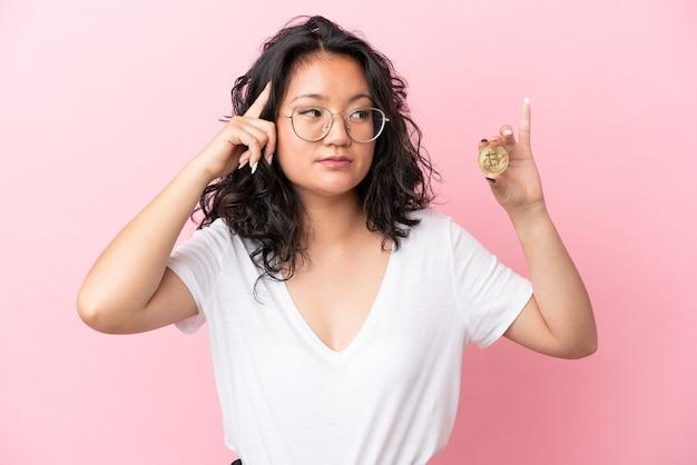 Jovem mulher asiática segurando um bitcoin isolado em um fundo rosa, tendo dúvidas e pensando