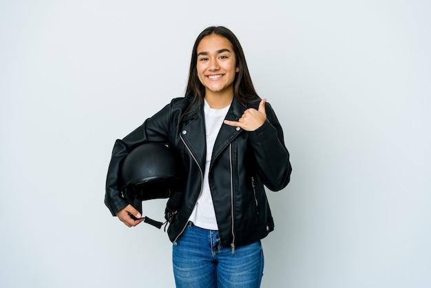Jovem mulher asiática segurando um capacete de moto, mostrando um gesto de chamada de telefone móvel com os dedos.