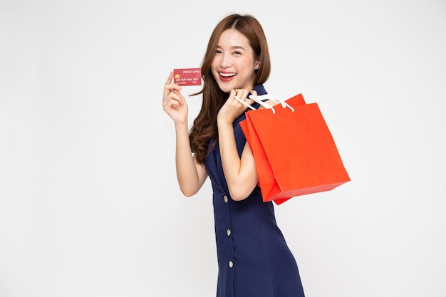Jovem mulher asiática segurando um cartão de crédito e sacolas vermelhas isoladas no fundo branco
