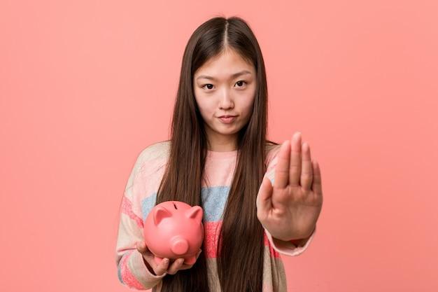 Jovem mulher asiática segurando um cofrinho em pé com a mão estendida, mostrando o sinal de stop, impedindo-o.