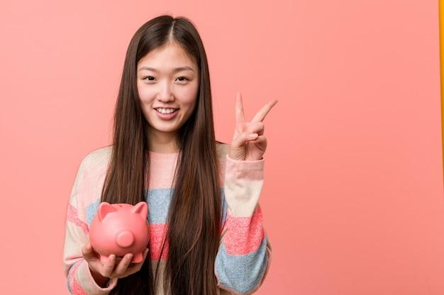 Jovem mulher asiática segurando um cofrinho mostrando o número dois com os dedos.
