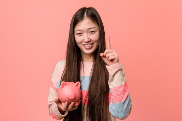 Jovem mulher asiática segurando um cofrinho mostrando o número um com o dedo.