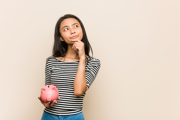 Jovem mulher asiática segurando um cofrinho, olhando de soslaio com expressão duvidosa e cética.