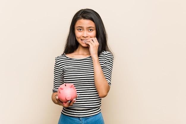 Jovem mulher asiática segurando um cofrinho roer unhas, nervoso e muito ansioso