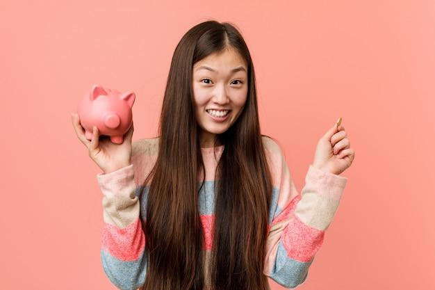 Jovem mulher asiática segurando um cofrinho