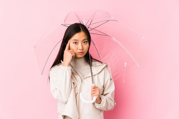 Jovem mulher asiática segurando um guarda-chuva apontando o templo com o dedo, pensando, focado em uma tarefa