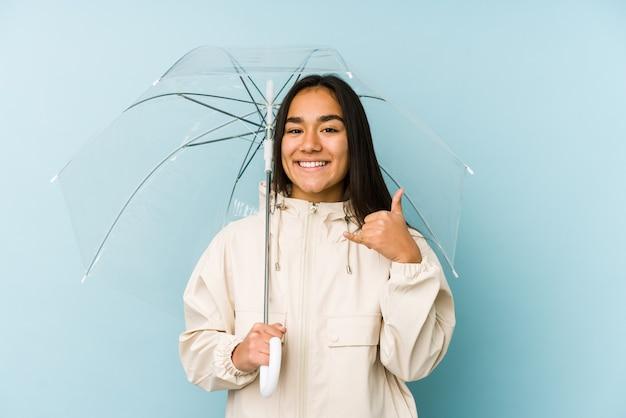 Jovem mulher asiática segurando um guarda-chuva, mostrando um gesto de chamada de celular com os dedos.
